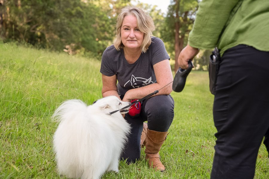 Photographer Jo Lyons smiling at the camera whilst greeting a client and her white Japanese Spitz