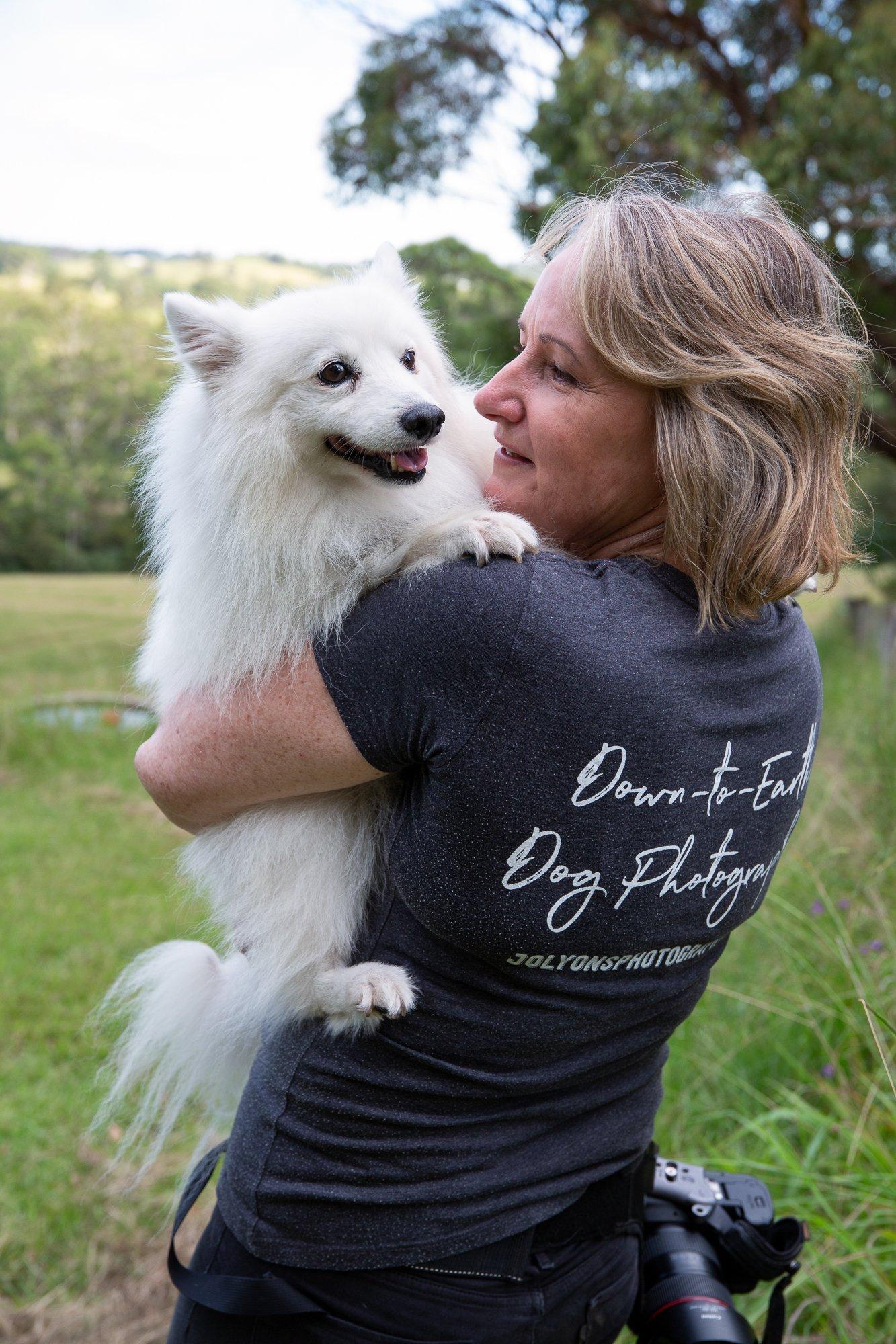 Jo Lyons the dog photographer holding a white Japanese Spitz dog